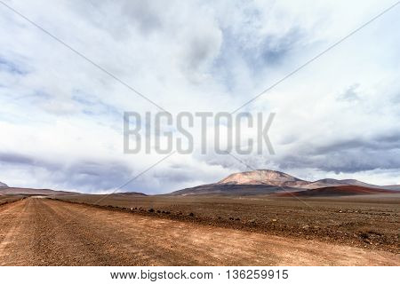 Dirt road on the Andes mountains (Chile) with San Francisco volcano on background