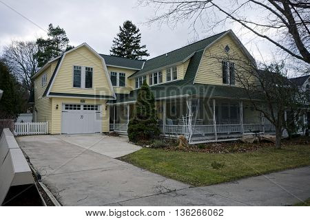 HARBOR SPRINGS, MICHIGAN / UNITED STATES - DECEMBER 24, 2015: An elegant yellow home with a wraparound porch and an attached garage near downtown Harbor Springs.