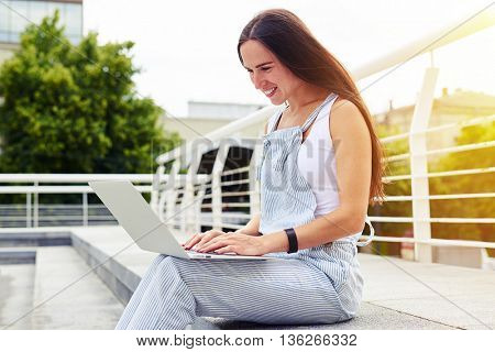 Dark-haired young woman is sitting on the pavement on the sunlit street with laptop on her knees
