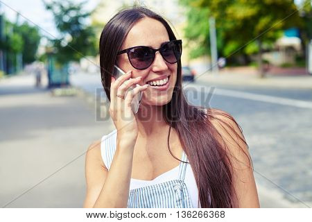Portrait of young attractive woman in sunglasses talking on the phone against city view background