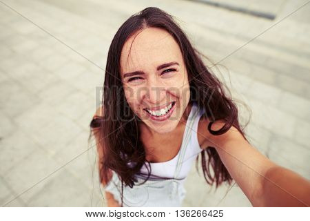 Young beautiful woman with ingenuous smile is making a selfie against pavement background
