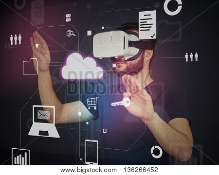 Young bearded man in virtual reality glasses is choosing icons on virtual interactive touch screen
