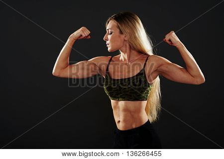 Portrait of sporty young sexy blonde showing her muscles isolated over black background