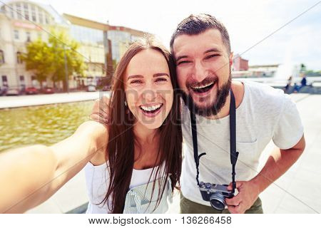 Happy young couple is smiling sincerely while making selfie in the recreational area of the city