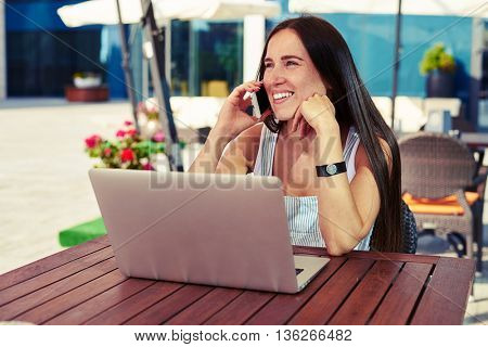 Beautiful smiling woman is sitting on a cafe terrace with laptop on the table and talking on the phone