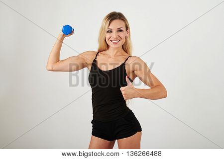 Sporty smiling blonde in sexy sportswear is holding a dumbbell and showing a thumb up gesture on white background