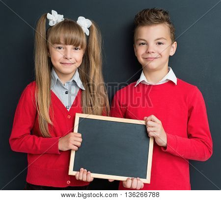 Happy pupil - teen boy and girl with small blackboard in front of a big chalkboard. Back to school concept.