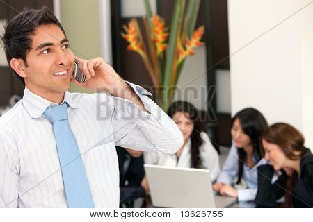 Business man talking on the phone and a group behing him
