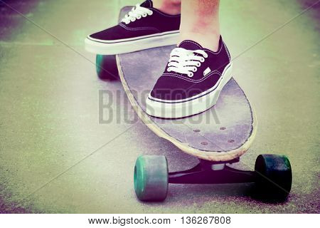 Girl standing on long board skateboard