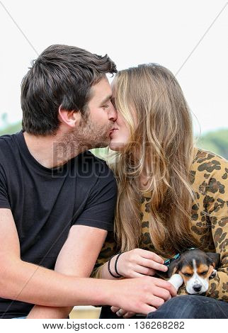 happy couple kissing with pet dog