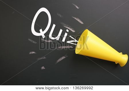 megaphone with message quiz on the blackboard