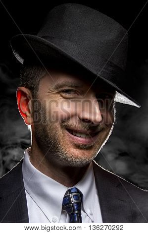 Man with a fedora hat posing as a film noir detective or gangster