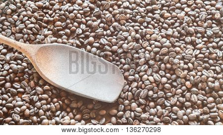 Roasted coffee beans in basket with wooden ladle. copy space.