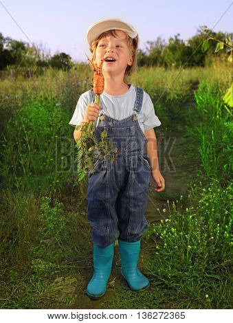 boy with a carrot in the summer garden outdoors