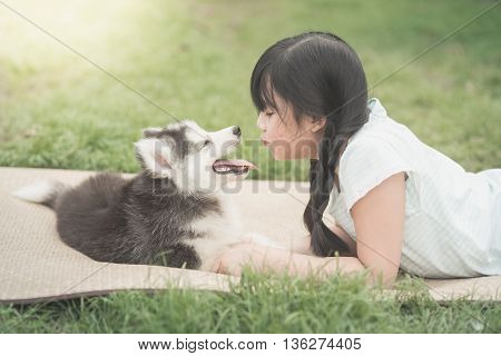 Beautiful asian girl playing with siberian husky puppy in the park vintage filter