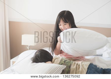 Happy Asian child having Pillow Fight in Hotel Room
