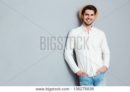 Portrait of a handsome man standing with arms in pockets isolated on a gray background