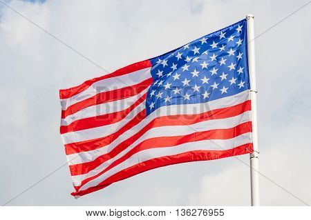 American flag waving against cloudy blue sky background focus on star of waving flag.
