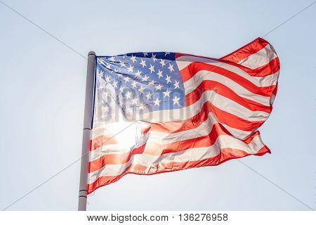 Close-up American flag flapping on sky with sunlight from back.