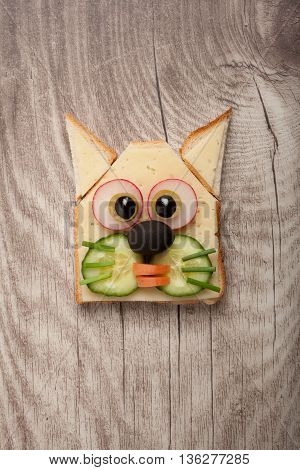 Funny cat made of toast and cheese on wooden background