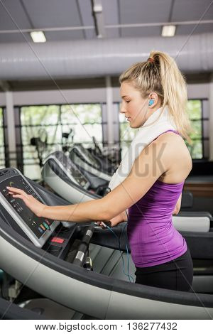 Woman listening to music on treadmill at gym