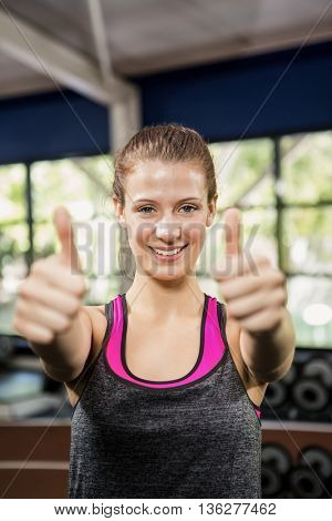 Happy woman showing her thumbs up while exercising at gym