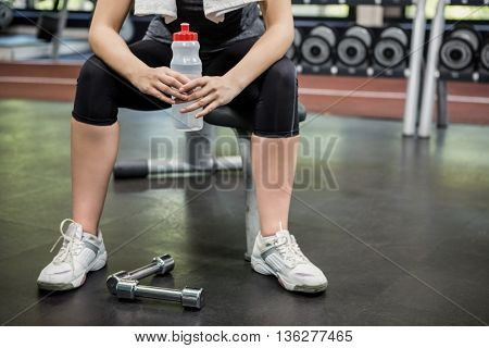 Woman sitting with a water bottle in gym