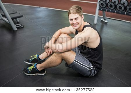 Handsome man sitting in weights room smiling