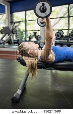 Woman lifting dumbbell weights while lying down in gym