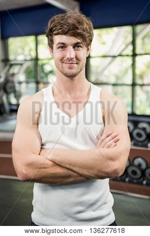 Portrait of handsome man standing in gym with hands crossed