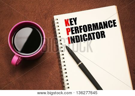 KPI Acronym - text on notebook with a pen and cup of coffee