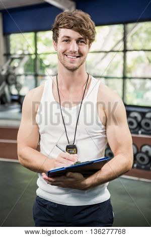 Portrait of male gym instructor writing on clipboard at gym