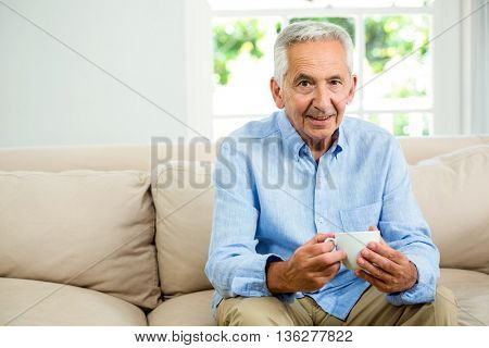 Portrait of smiling senior man holding coffee cup while sitting on sofa at home