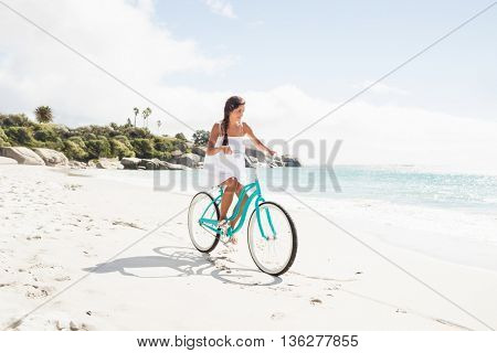 Carefree woman going on a bike ride on the beach