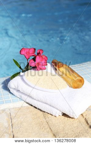 massage oil shellfish and white towel beside a pool