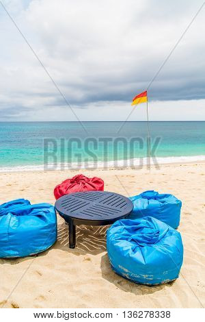 Four bean bags on the beach by the seashore with a table and some dark clouds over the water.