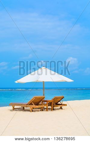 Daybed on a tropical white sand beach in Bali with the aqua colored water reaching to the horizon