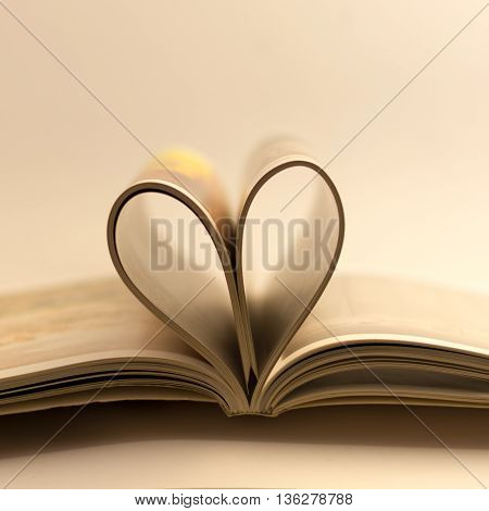A bound book with the pages creating a love heart shape.