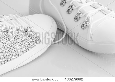 Women's white studded stylish shoes with a white background.
