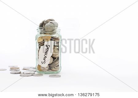 A glass jar overflowing with coins and spilling onto a white background