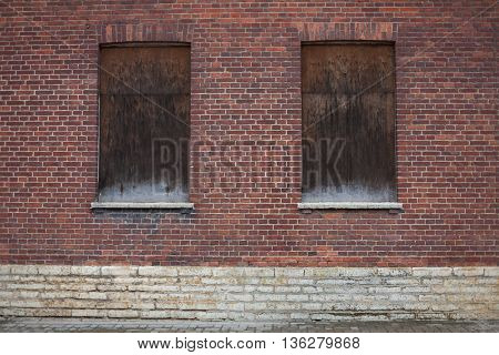 Windows closed shut on a dark red brick house