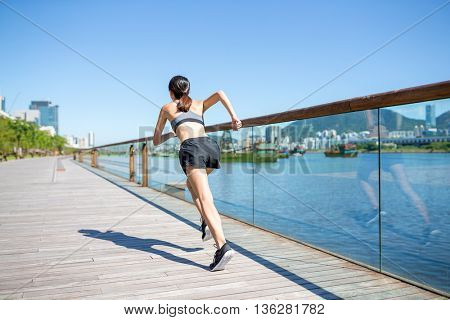 Back view of woman running on boardwalk
