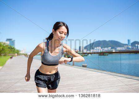 Woman using wearable watch in seaside boardwalk