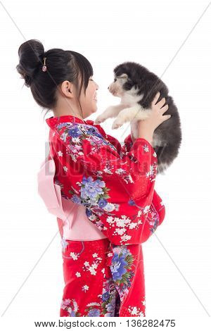 Little asian girl in red kimono playing with a siberian husky puppy on white background isolated