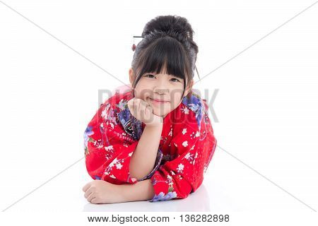 Beautiful Asian girl in red kimono lying on white background isolated