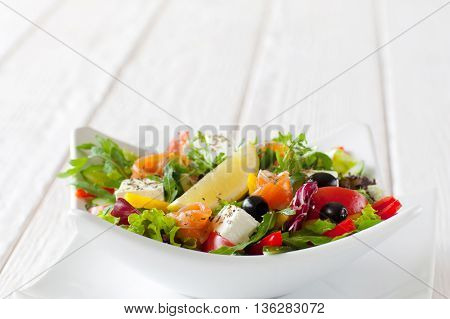 Fresh vegetable salad with salmon in white bowl copyspace. Front view on white ceramic bowl with tasty salad with salmon, brie, olives and slice of lemon on white wooden background. Free space