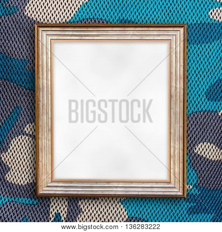 Blank of wooden photo frame on military pattern fabric background.