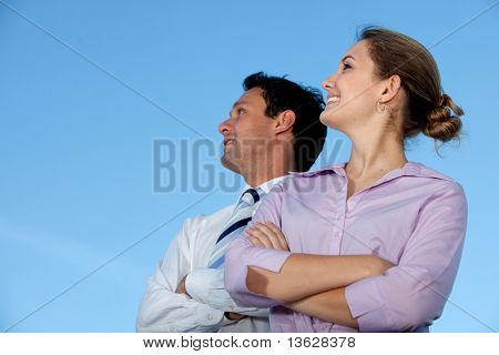 Business couple smiling and looking at the sky