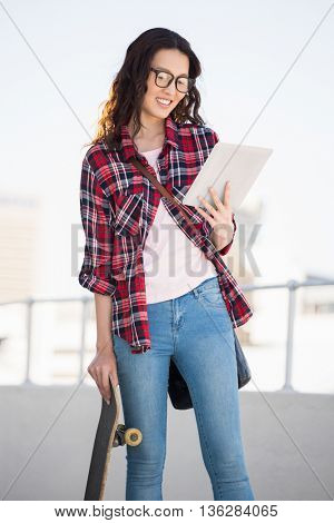 Hipster with skateboard and tablet in the city