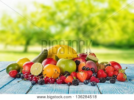 Fresh fruit pile placed on wooden planks, blur garden on background. Concept of healthy eating, antioxidants and summer time.